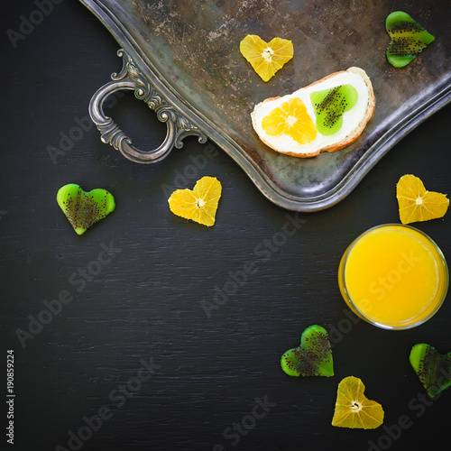 Sandwich made of citrus with kiwi fruit and fresh juice on dark. Flat lay, top view. Copy space