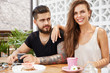 Fashionable female and male friends have good relationship, glad to meet with each other at coffee shop, have pleasant friendly talk with cup of hot beverage, share news, look happily into camera