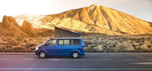 Small travel vehicle camping van or big car with folding rooftop with bed is parked under huge mountain formation. Tourism vacation and travel. Camper van and mountains landscape