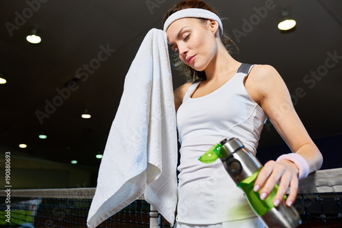 Fotobehang Tennis Waist up portrait of female tennis player wiping forehead with towel taking break from practice in indoor court, copy space