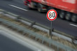 Defocused image of traffic sign showing speed limit on a highway with truck driving in the background