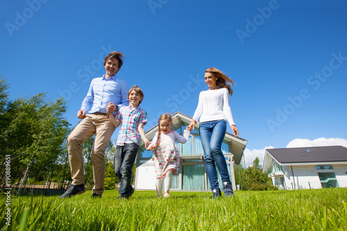 Family running on lawn near house