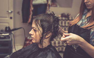 A professional hairdresser cuts hair to a woman in a beauty salon. The process of creating a stylish hairstyle.