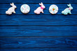 Easter bunny and easter eggs cookies. Easter symbols and traditions. Blue wooden background top view copy space