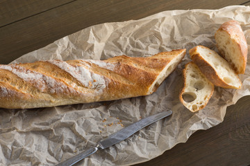 A baguette on a wooden background.