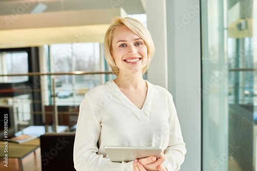 Waist-up portrait of pretty blond-haired manager looking at camera with wide smile while holding digital tablet in hands, interior of spacious office lobby on background