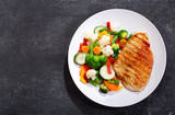 plate of grilled chicken with vegetables, top view