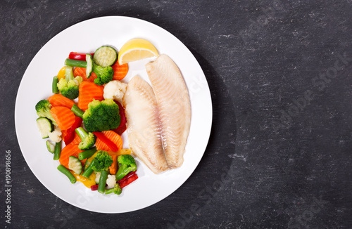 plate of fried fish fillet with vegetables, top view