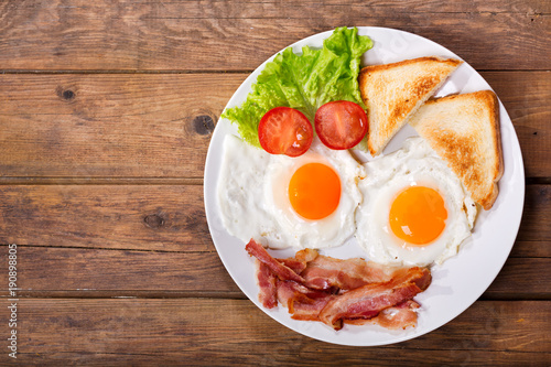plate of fried eggs with bacon on wooden table, top view