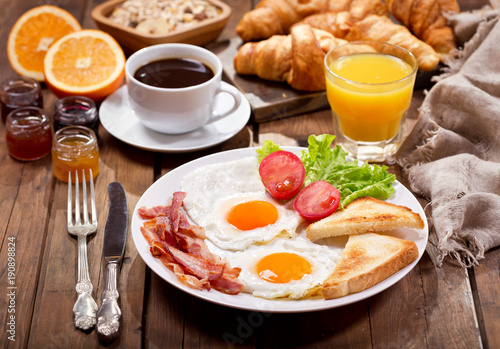 breakfast with fried eggs, coffee, juice and fresh fruits
