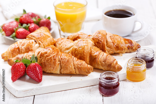 breakfast with croissants, juice, coffee and fruits