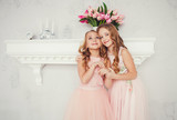 portrait of two embracing cute little girls in dresses - 190901407