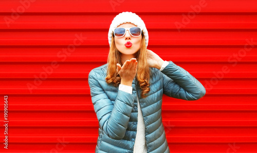 Fashion woman blowing red lips sends an air kiss on a background - 190905643
