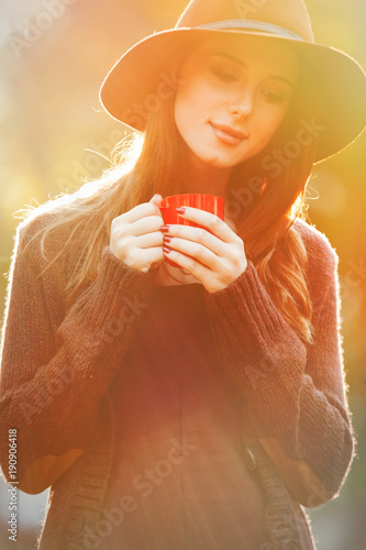 Young redhead woman with cup of tea and hat standing at outdoor with sunlights
