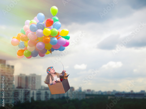 Happy girl flying in a cardboard box on the balloons. Flying high above the city
