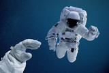 Astronaut reaching out for colleague during space walk