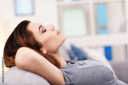 Relaxed young woman enjoying rest on comfortable sofa