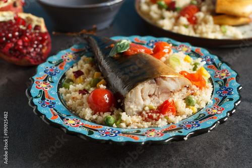 Moroccan food with couscous, smoked fish and vegetables on traditional plate