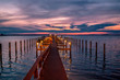 A colorful Dunedin, Florida USA sunset with the repetitious poles of a pier reaching out into the purple distance.