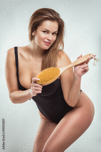 Portrait of a beautiful young woman in a swimsuit with an anti-cellulite massage brush