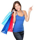 Shopping woman excited about new purchases or sale holding blue and red shopping bags pointing to the side copy space. Happy multiracial model in studio cutout portrait isolated on white background. - 190934019