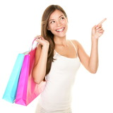 Asian shopping girl looking up pointing to the side for product advertisement. Happy multiracial model holding pink and blue pastel color shopping bags isolated on white background. - 190934081