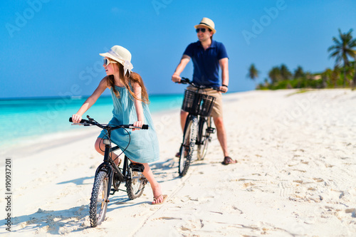 Father and daughter riding bikes at tropical beach