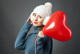 Beauty  Young fashion model Girl with Valentine Heart shaped baloon in hand. Love. Beautiful young woman , advertising gesture. Valentines Day gift. - 190944854