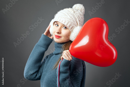 Beauty  Young fashion model Girl with Valentine Heart shaped baloon in hand. Love. Beautiful young woman , advertising gesture. Valentines Day gift.