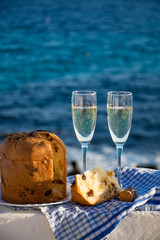 Sweet fruit Chrismas and Easter cake panettone with two glasses with champagne served outside near blue sea