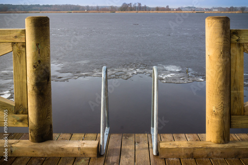 Acrylglas Pier Wooden Platform On The Side Of Frozen Lake In Polish Countryside