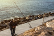 Fisherman in cap and blouse on deck with his fishing rod with reel changing the bait