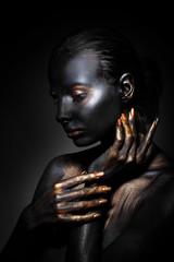 young girl with black skin with golden lips in the middle of a black background