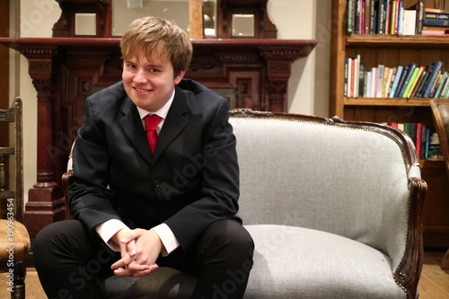 A young man smiling in a suit sat on a sofa.