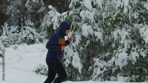 slow motion man of young runner Sportsman Running Through Snowy Forest. shot side view winter tree forest in the snow