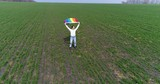 Excited woman standing in the field with LGBT pride flag - 190966211