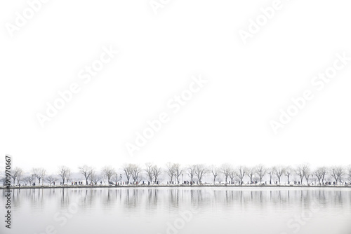 Landscape at Xihu Lake, Hangzhou, China, people walking across the lake while snowing in a winter day, reflection at the lake