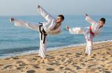 Man and boy doing karate poses