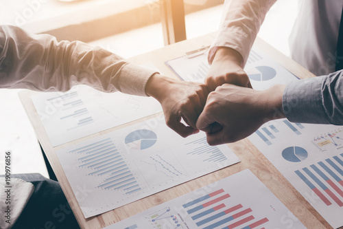 young-business-teamwork-giving-fist-bump-for-success-project-and-chart-report-on-desk