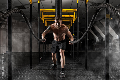 Wall mural Man working out with battle ropes at gym