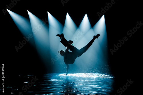 Performance on the water of a dance group against the background of club light. © fotofrol