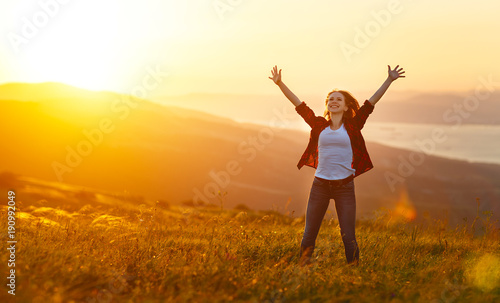Foto Murales Happy woman   on sunset in nature iwith open hands