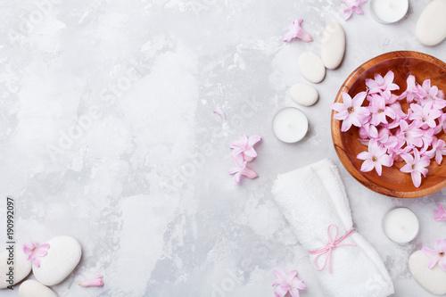 Aromaterapia, piękno, tło spa z kamykiem do masażu, perfumowane kwiaty wody i świec na kamienny blat widok. Relaks i zen jak koncepcja. Płaskie leżało.