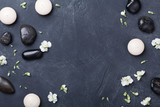 Composition for aromatherapy or spa decorated flowers on black stone background top view. Beauty treatment and relaxation concept. Flat lay. .