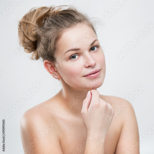 Portrait of a beautiful young woman on a gray background
