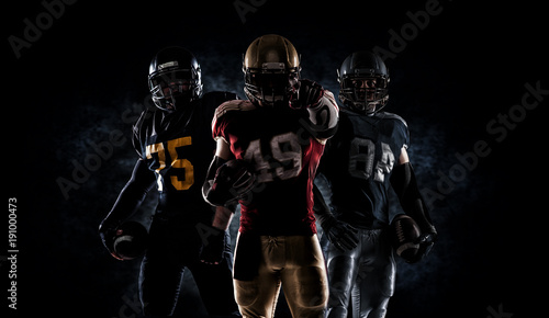 American football players holding ball while running on field at night