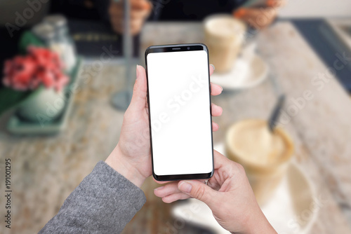 Smart phone mockup in woman hands. Coffee shop in background, table and plant. Big screen with round edges. - 191001295