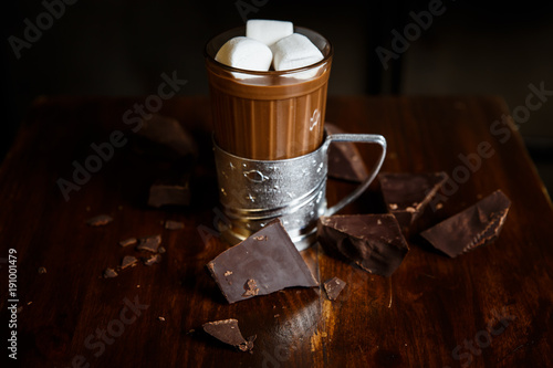 Fotobehang Chocolade An underexposed horizontal image of hot chocolate in a glass in a metal glass-holder, decorated with marshmallows and pieces of dark chocolate on a wooden table. Selective focus.