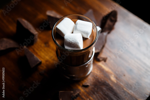 Deurstickers Chocolade An underexposed horizontal image of hot chocolate in a glass in a metal glass-holder, decorated with marshmallows and pieces of dark chocolate on a wooden table. Selective focus.