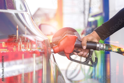 Put in gasoline car fuels, Oil station and fuel nozzle in car with power plants background